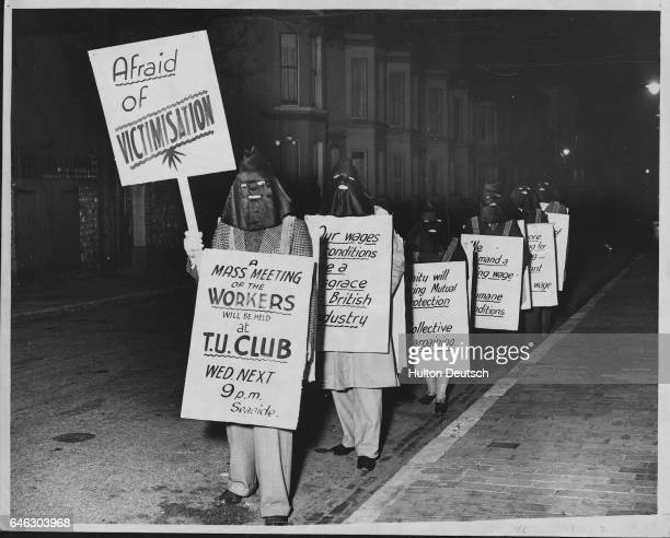 Members of the new Eastbourne Hotel Workers' Union parade the streets and seafront to air their grievances They are hooded to prevent identification