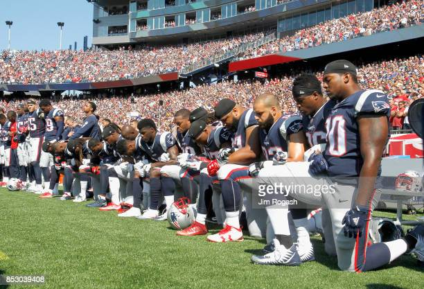 Members of the New England Patriots kneel during the National Anthem before a game against the Houston Texans at Gillette Stadium on September 24,...