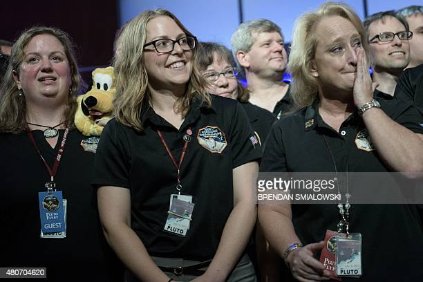 Members of the New Horizons mission team listen to a press conference at the Johns Hopkins University Applied Physics Laboratory in Laurel Maryland...