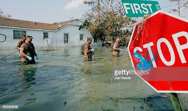 Members of the New Mexico National guard wade through water to check for bodies in homes destroyed after Hurricane Katrina passed through September...