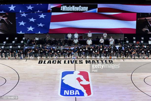 Members of the New Orleans Pelicans and Utah Jazz kneel before a Black Lives Matter logo before the start of their game at HP Field House at ESPN...