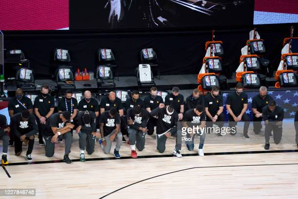 Members of the New Orleans Pelicans and Utah Jazz kneel during the national anthem before the start of their game at HP Field House at ESPN Wide...
