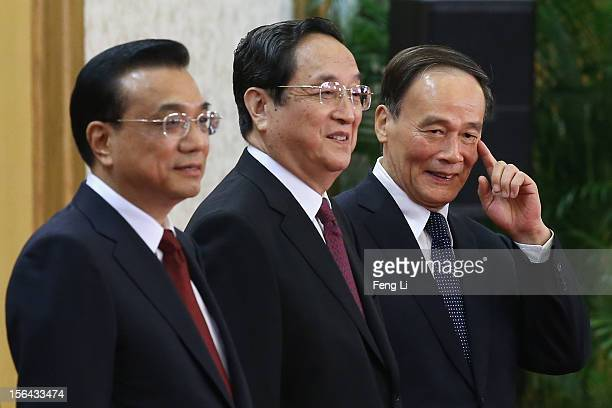 Members of the new Politburo Standing Committee Li Keqiang Yu Zhengsheng and Wang Qishan greet the media at the Great Hall of the People on November...