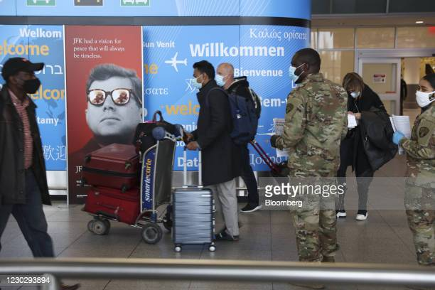 Members of the New York Army National Guard greet travellers arriving at John F. Kennedy International Airport in New York, U.S., on Thursday, Dec....