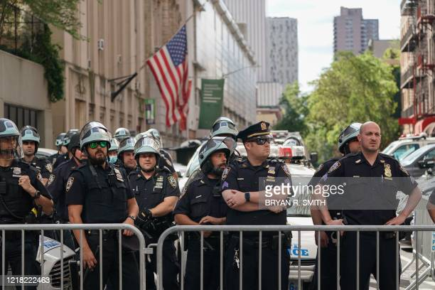 Members of the New York City Police Department look on from the Midtown North Precinct as Black Lives Matter protesters march in midtown over the...