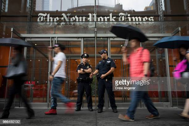 Members of the New York City Police Department stand outside the headquarters of The New York Times, June 28, 2018 in New York City. NYPD announced...