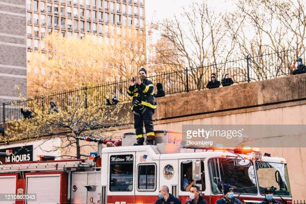 Members of the New York Fire Department wearing protective masks gather outside New York University Langone Health hospital to applaud the medical...