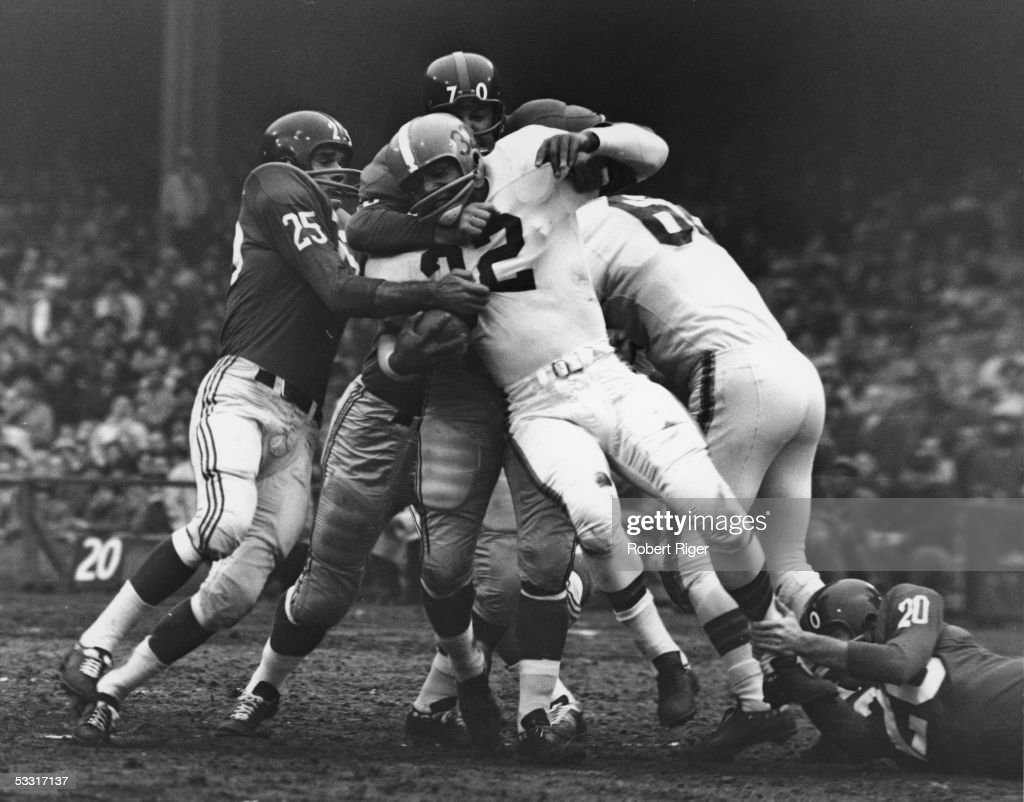 Members of the New York football Giants defensive squad take down American professional football player Jim Brown (center) #32 of the Cleveland Browns during a game at Yankee Stadium, New York, December 12, 1957. The BRowns went on to win 34 to 28.