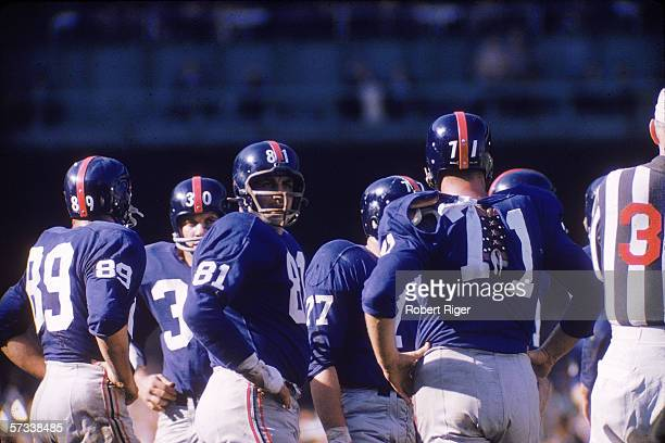 Members of the New York Giants football team stand on the field with their hands on their hips as they wait for the next plays during a home game...