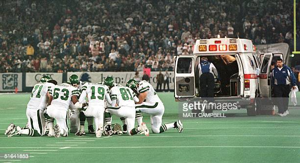 Members of the New York Jets kneel in a circle and pray as Detroit Lions linebacker Reggie Brown is taken away in an ambulance by medical personnel...