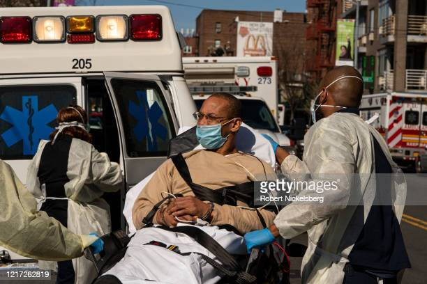 Members of the New York Police Department transport a sick prisoner in handcuffs to a private ambulance outside the emergency room of the Elmhurst...