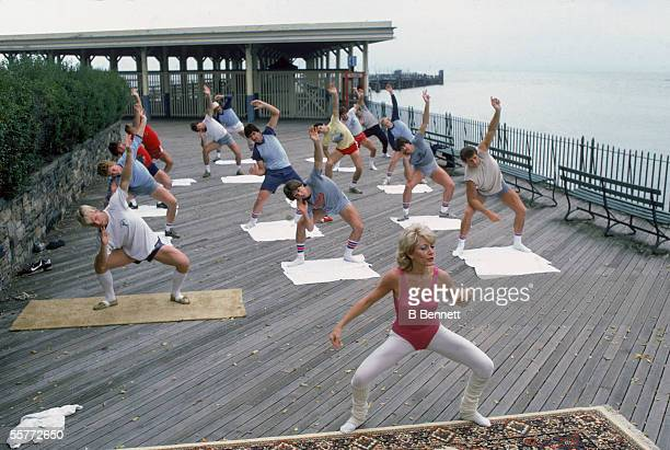 Members of the New York Rangers ice hockey team warm up with an aerobics instructor at on a boardwalk during training camp Rye New York September 1982