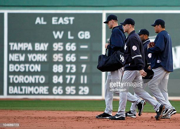Members of the New York Yankees bullpen walk off of the field after losing to the Boston Red Sox 84 at Fenway Park October 3 in Boston Massachusetts...