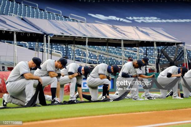 Members of the New York Yankees kneel and hold a black ribbon to show their support for social justice and diversity and inclusion in baseball and...