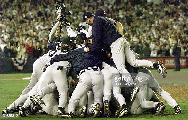 Members of the New York Yankees pile on each other after winning game four of the World Series against the San Diego Padres 21 October at Qualcomm...