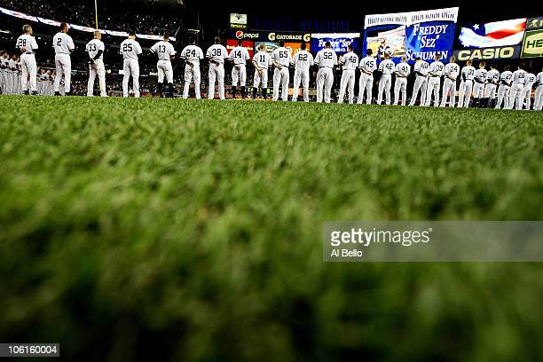Members of the New York Yankees stand in silence as they remember deceased Yankee fan Freddy Freddy Sez Schuman before playing against the Texas...
