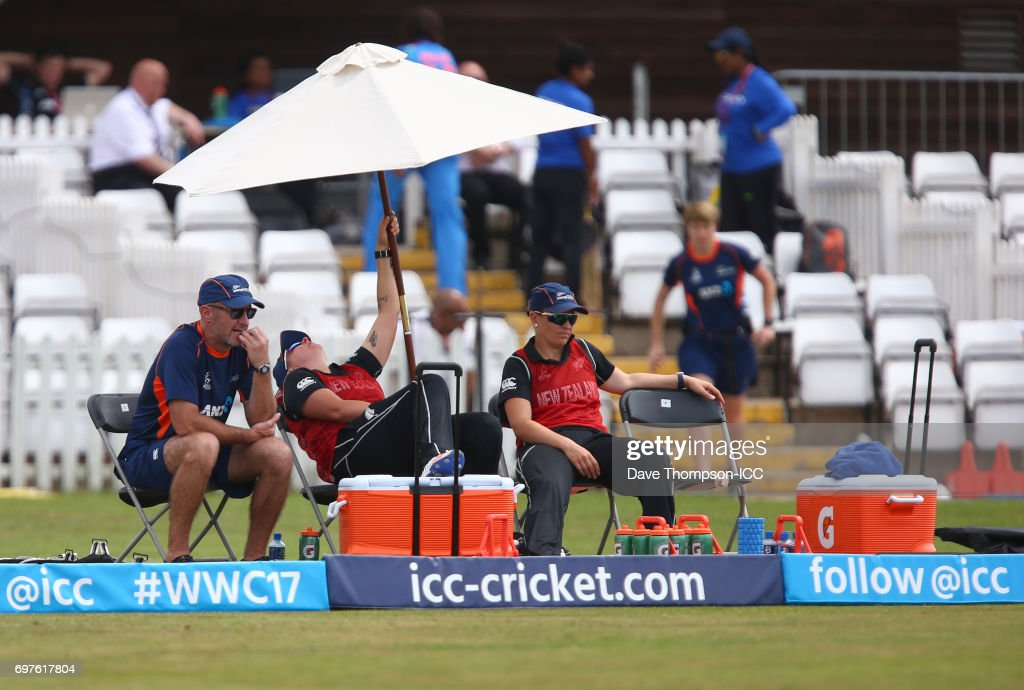Members of the New Zealand staff shelter from the sun under an umbrella during the ICC Women's World Cup warm up match between India and New Zealand at The County Ground on June 19, 2017 in Derby, England.