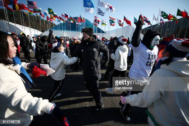 Members of the New Zealand team dance with performers and volunteers after the team's flag raising ceremony during previews ahead of the PyeongChang...
