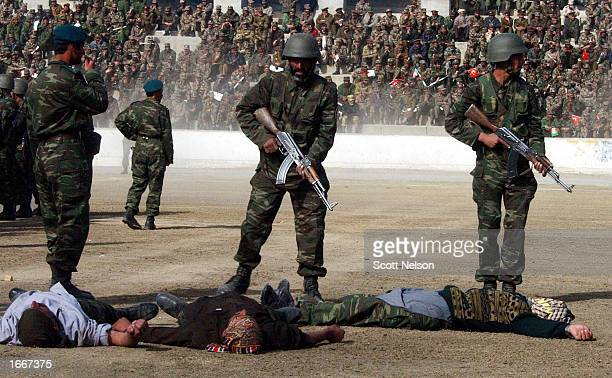 Members of the newly trained 1st Battalion Afghan National Guard stand over mock casualties during a demonstration of their riot control skills at...