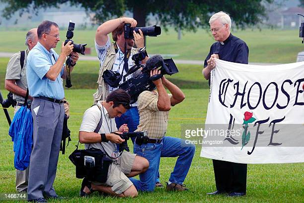 Members of the news media photograph Father Fred Ruse of Winter Haven Florida holding a banner reading Choose Life before the execution of Aileen...