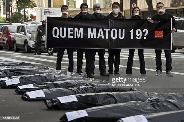 """Members of the NGO Rio da Paz hold a banner that reads """" Who Killed the 19?"""" during a demonstration in Sao Paulo, Brazil, on August 28, 2015...."""