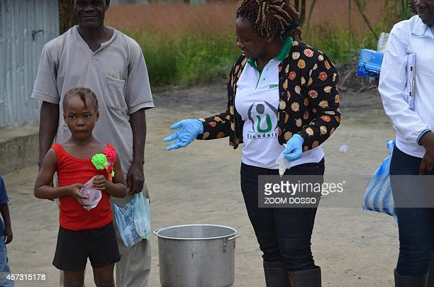 Members of the NGO U Fondation give medication on October 16 2014 in Monrovia to a child whose quarantined family members are suffering from the...