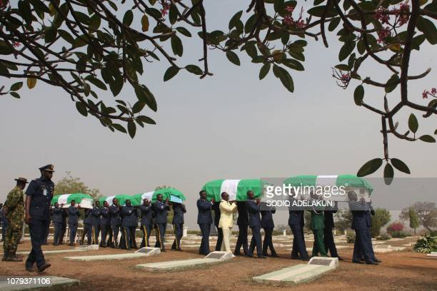 TOPSHOT Members of the Nigerian air force carry the coffins of five of their comrades who died in a helicopter crash in Nigeria's Borno State during...