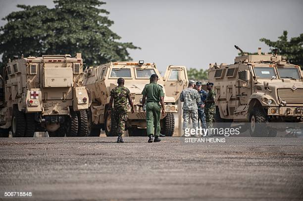 Members of the Nigerian and United States military discuss as they stand next to some of the 24 armoured vehicles donated to the Nigerian government...