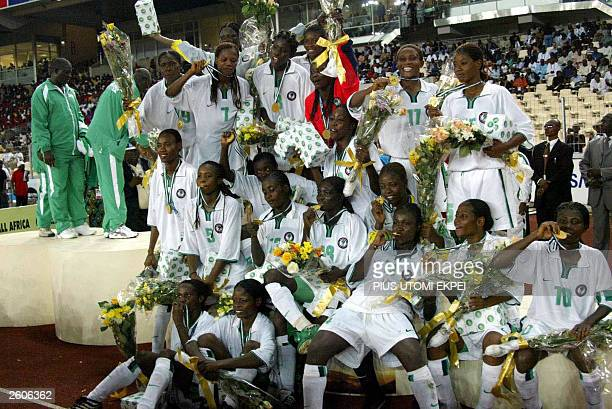 Members of the Nigerian women's soccer team pose on the podium with their medals late 16 October 2003 after winning the All Africa Games final over...