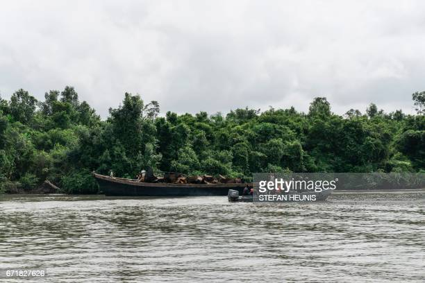 Members of the NNS Delta of the Nigerian Navy forces escorts a transport boat filled with destroyed illegal oil refinery storage tanks on April 19...