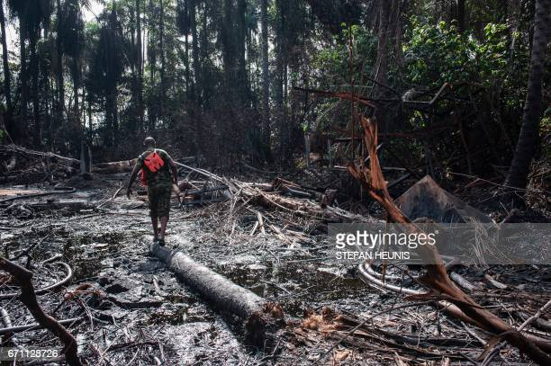 TOPSHOT A members of the NNS Pathfinder of the Nigerian Navy forces walks through the oil covered environment of a destroyed illegal oil refinery on...
