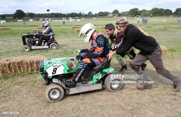 Members of the Nobby Racing team push one of their riders out from the pits during qualifying for the British Lawn Mower Racing Association 12 hour...