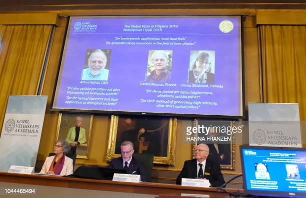 Members of the Nobel Committee for Physics Olga Botner Goran K Hansson and Mats Larsson sit in front of a screen displaying portraits of Arthur...