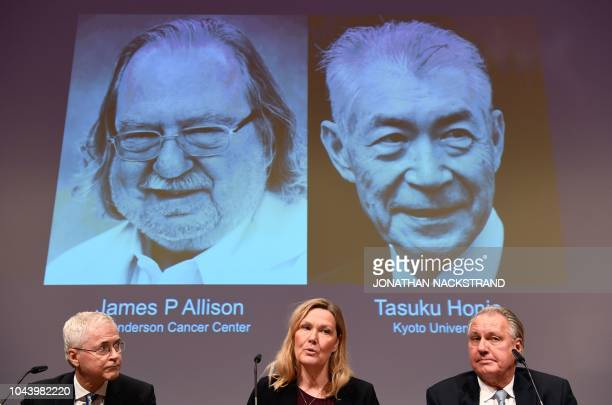 Members of the Nobel Committee for Physiology or Medicine Edvard Smith Anna Wedell and Klas Kaerre sit in front of a screen displaying portraits of...