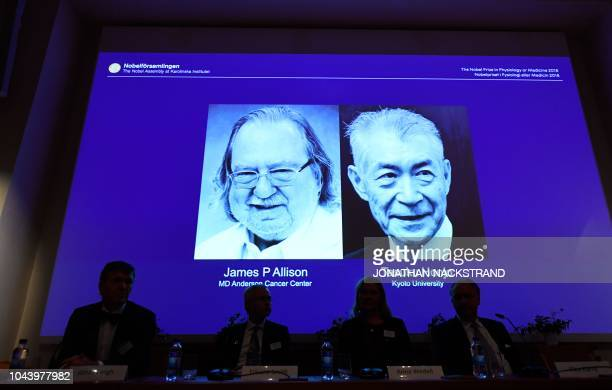 Members of the Nobel Committee for Physiology or Medicine sit in front of a screen displaying James P Allison and Tasuku Honju the winners of the...