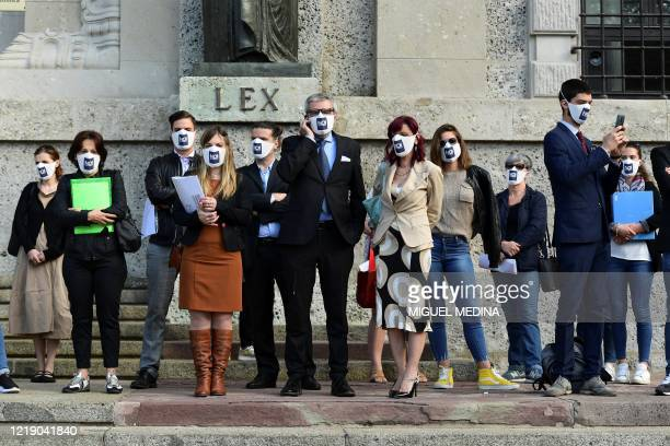 """Members of The """"Noi Denunceremo"""" committee mostly relatives of covid-19 victims wearing protection masks bearing the """"Noi Denunceremo"""" inscription..."""