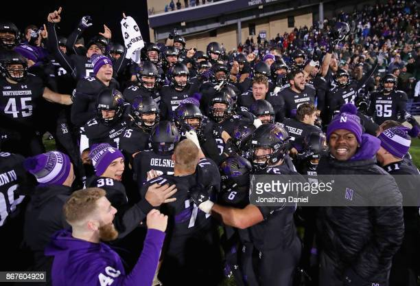 Members of the Northwestern Wildcats celebrate a triple overtime win against the Michigan State Spartans at Ryan Field on October 28 2017 in Evanston...