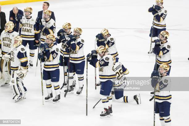 Members of the Notre Dame Fighting Irish watch as the University of Minnesota Duluth Bulldogs celebrates during the Division I Men's Ice Hockey...