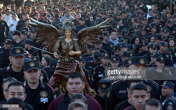 Members of the Nuevo Leon state police carry the image of Archangel Gabriel during a procession to thank him for taking care of them during their...
