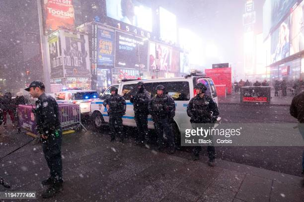 Members of the NYPD in full counterterriorism attire stand while the snow squall comes through Times Square in the Manhattan borough of New York on...