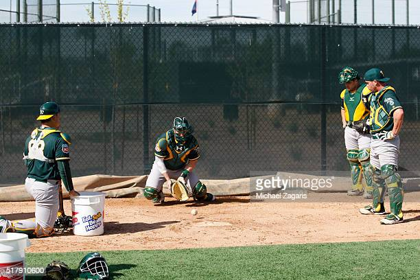 Members of the Oakland Athletics go through catcher drills during a spring training workout at Fitch Park on March 1 2016 in Mesa Arizona
