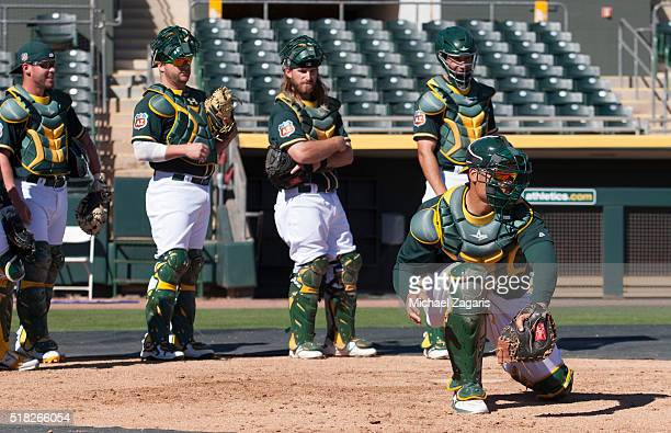 Members of the Oakland Athletics go through catcher drills prior to a spring training game against the Los Angeles Dodgers at Hohokam Stadium on...