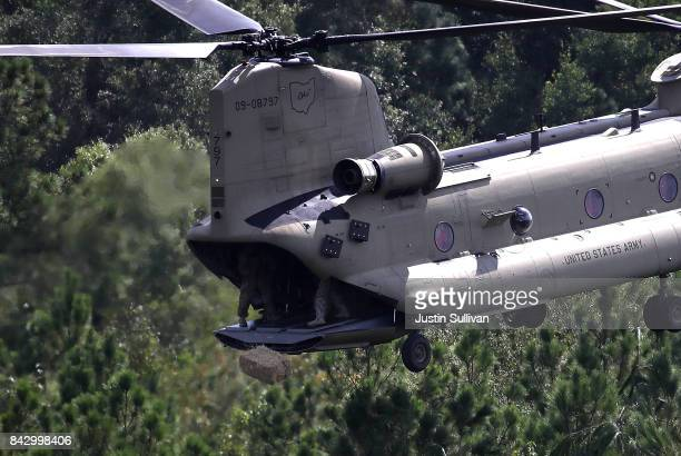 Members of the Ohio Army National Guard drop a bale of hay from the back of a CH74 Chinook helicopter on September 5 2017 near Beaumont Texas The...