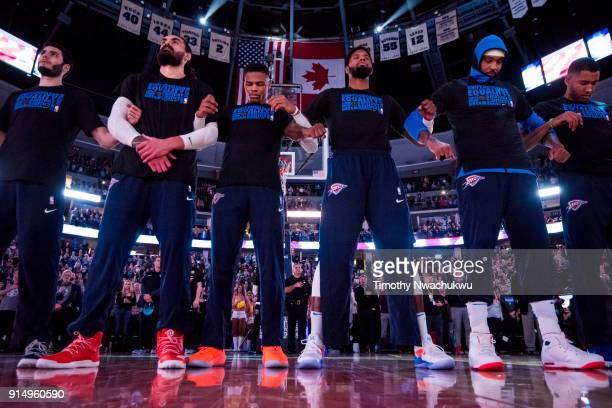 Members of the Oklahoma City Thunder stand during a playing of the United States national anthem at Pepsi Center on February 1 2018 in Denver...
