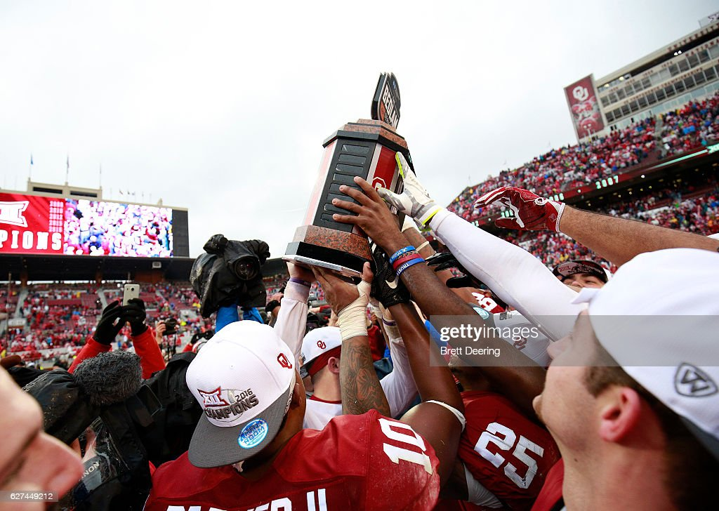 Members of the Oklahoma Sooners hold up the Bedlam Trophy after the game against the Oklahoma State Cowboys December 3, 2016 at Gaylord Family-Oklahoma Memorial Stadium in Norman, Oklahoma. Oklahoma defeated Oklahoma State 38-20 to become Big XII champions.