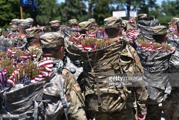 Members of the Old Guard arrive with packs full of US flags to place on graves at Arlington National Cemetery on May 24 2018 ahead of Memorial Day in...