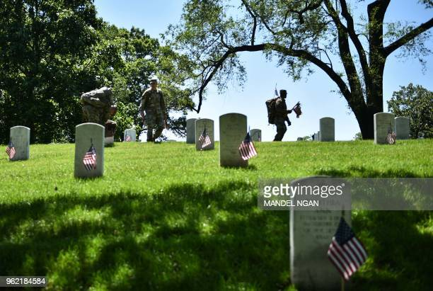 TOPSHOT Members of the Old Guard place US flags on graves at Arlington National Cemetery on May 24 2018 ahead of Memorial Day in Arlington Virginia