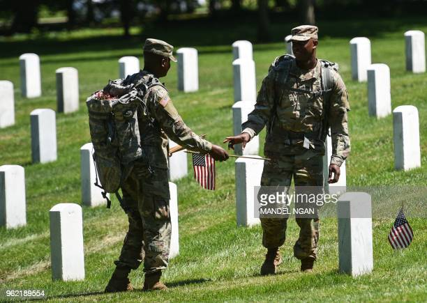 Members of the Old Guard place US flags on graves at Arlington National Cemetery on May 24 2018 ahead of Memorial Day in Arlington Virginia