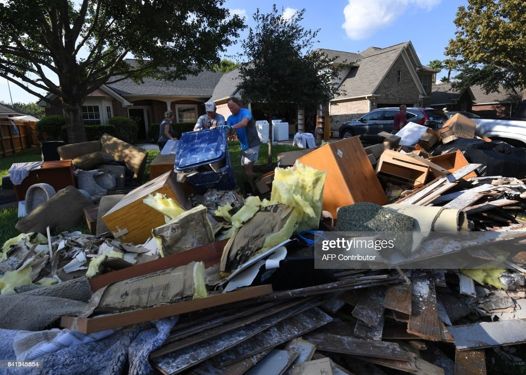 TOPSHOT - Members of the Olson family remove debris and damaged items from their father's home in the Twin Oaks Estate after Hurricane Harvey caused widespread flooding in Houston, Texas on August 31, 2017. In Houston, America's fourth-largest city, some of the 2.3 million residents got relief as the raging waters receded. But in several other towns in the Lone Star State doused by days of torrential rains since Harvey smashed into the US Gulf Coast almost a week ago as a Category Four hurricane, the situation was dire. RALSTON