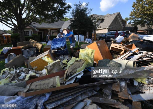 TOPSHOT Members of the Olson family remove debris and damaged items from their father's home in the Twin Oaks Estate after Hurricane Harvey caused...